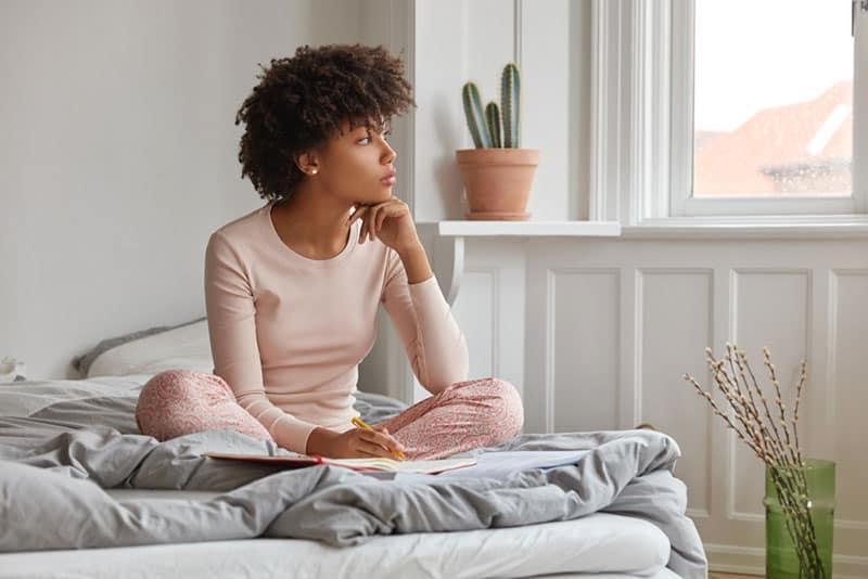 nachdenkliche Frau sitzt auf dem Bett