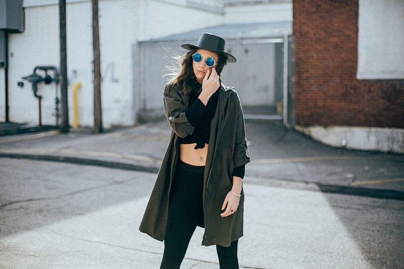 nette Frau posiert mit Hut und Brille