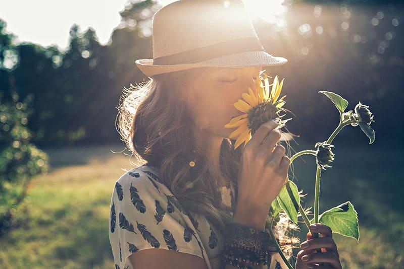 nettes Mädchen, das eine Blume in der Natur riecht