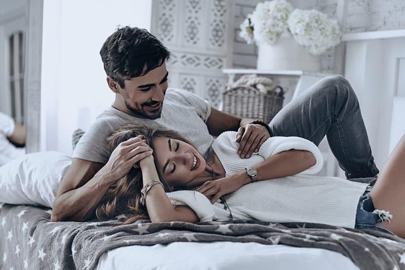 nettes Paar, das auf dem Bett liegt