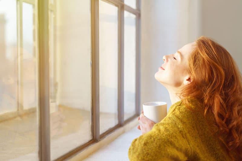 rote Frau, die am Fenster mit Kaffee genießt