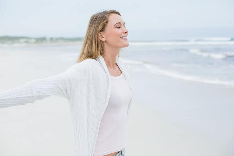ruhige Frau, die ihre Arme am Strand ausbreitet
