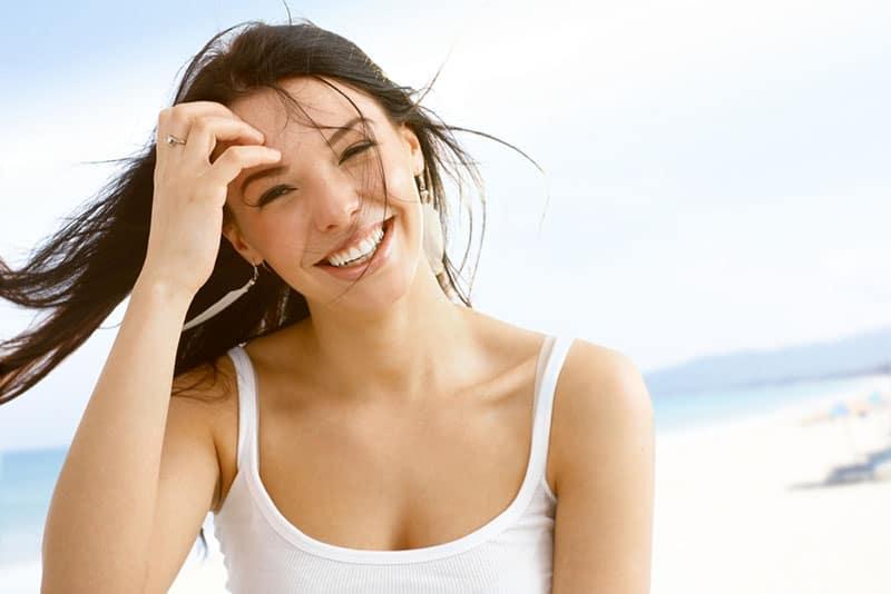 süße Frau, die am Strand lächelt