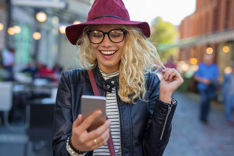 süße blonde Frau mit lila Hut