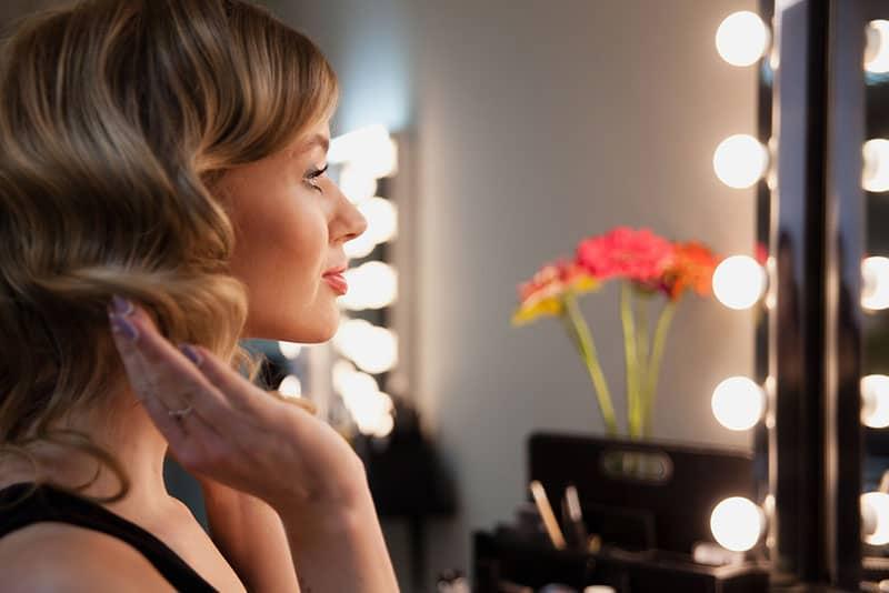 schöne Frau, die die Spiegel betrachtet