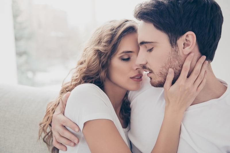 schöne junge Blondine mit ihrem Mann küssen