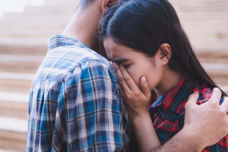 traurige Frau, die auf Mannschulter weint