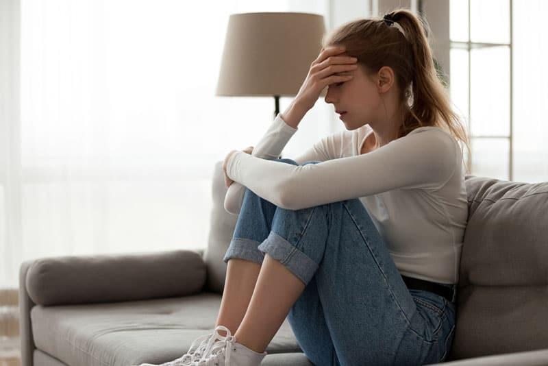 traurige Frau, die auf dem Boden sitzt und ihren Kopf hält