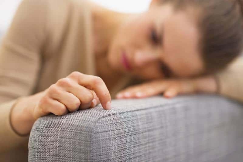 traurige Frau, die im Wohnzimmer liegt und denkt