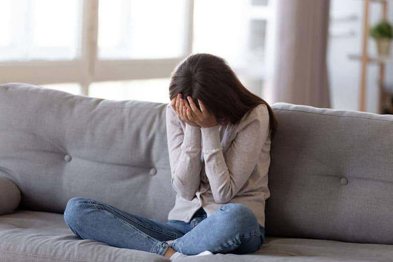 traurige Frau sitzt auf dem Bett und hält ihren Kopf
