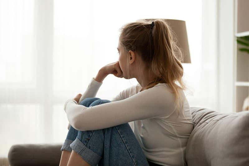 traurige blonde Frau, die auf dem Sofa sitzt