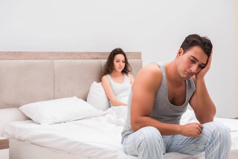 trauriges Paar, das auf dem Bett im Schlafzimmer sitzt