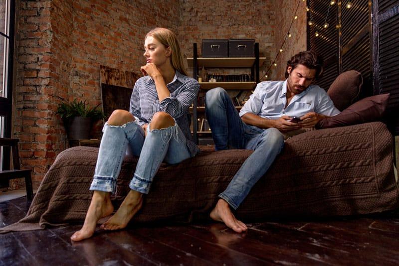 trauriges Paar das auf der Couch sitzt redet nicht