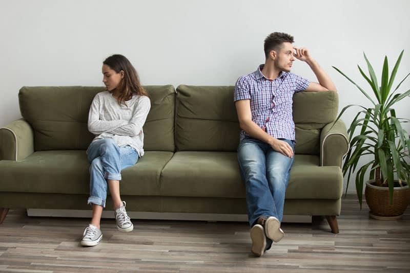 trauriges Paar, das separat im Wohnzimmer sitzt