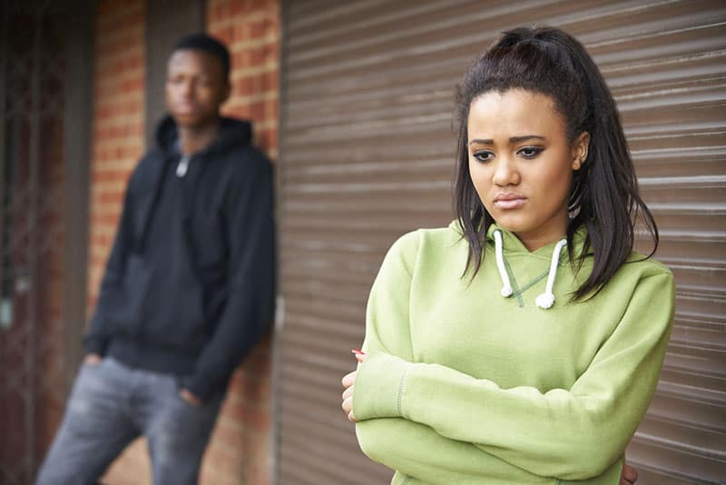 unglückliches Mädchen, das draußen vor ihrem Freund steht