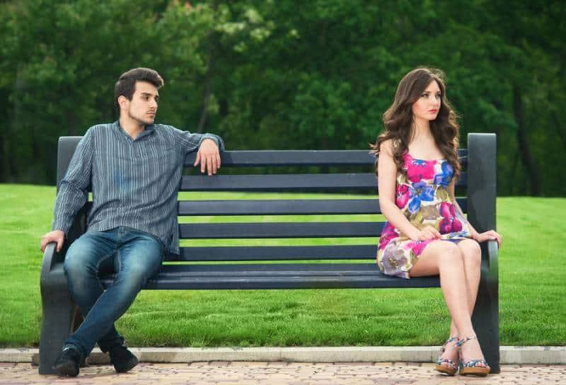 unglückliches Paar, das im Park auf der Bank sitzt