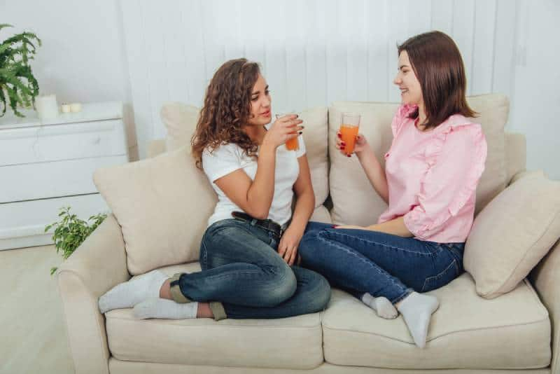zwei Freundinnen, die sich im Wohnzimmer unterhalten