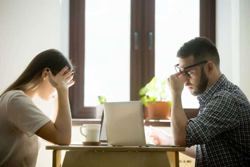 zwei Paare sitzen mit Stress am Schreibtisch