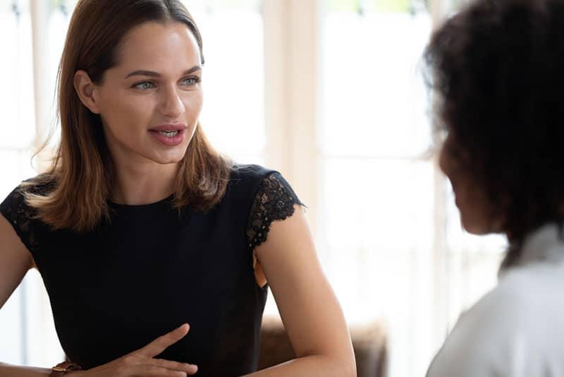 zwei junge Frau sprechen im Büro