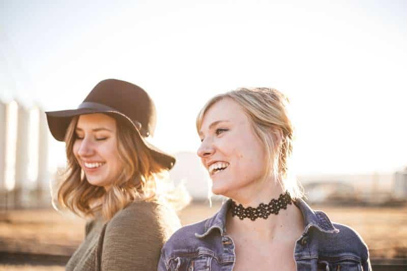 zwei lächelnde Frauen, die nach draußen gehen