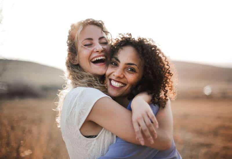 zwei lächelnde Freundinnen, die sich draußen umarmen