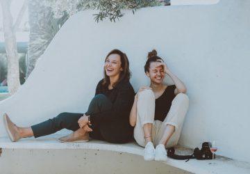 zwei Frauen lachen auf der Bank