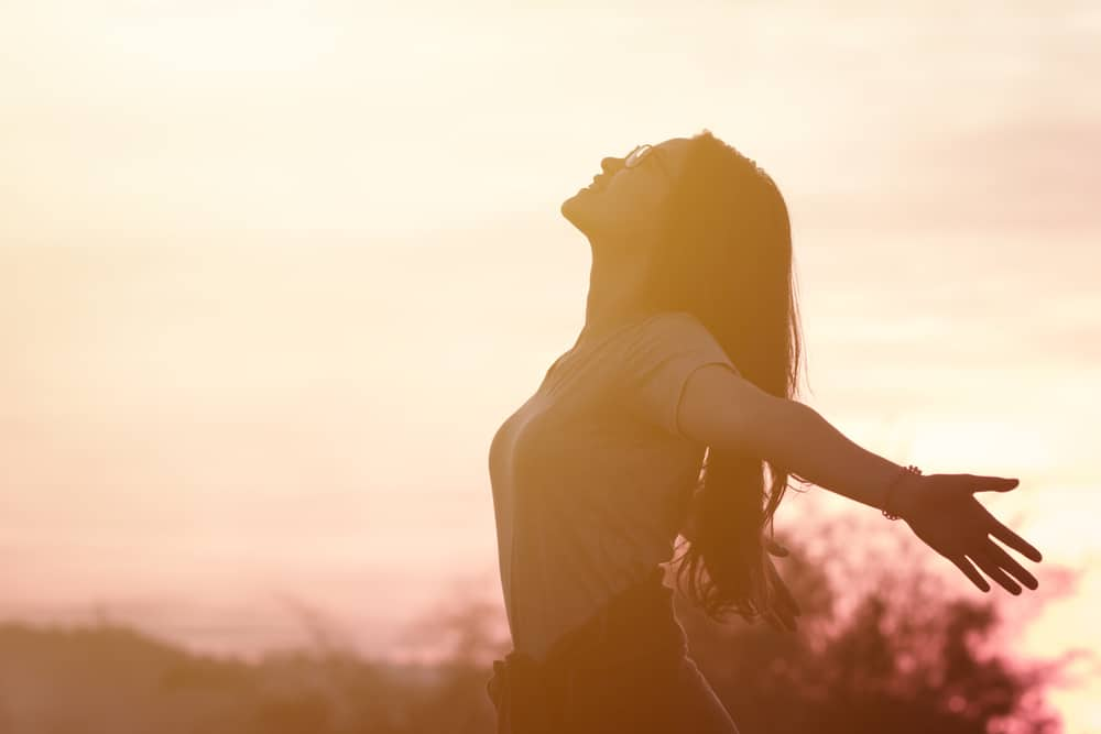 Frau fühlt sich draußen bei Sonnenuntergang fantastisch