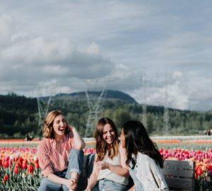 3 Frauen sitzen auf einer Bank in der Nähe der Blumen