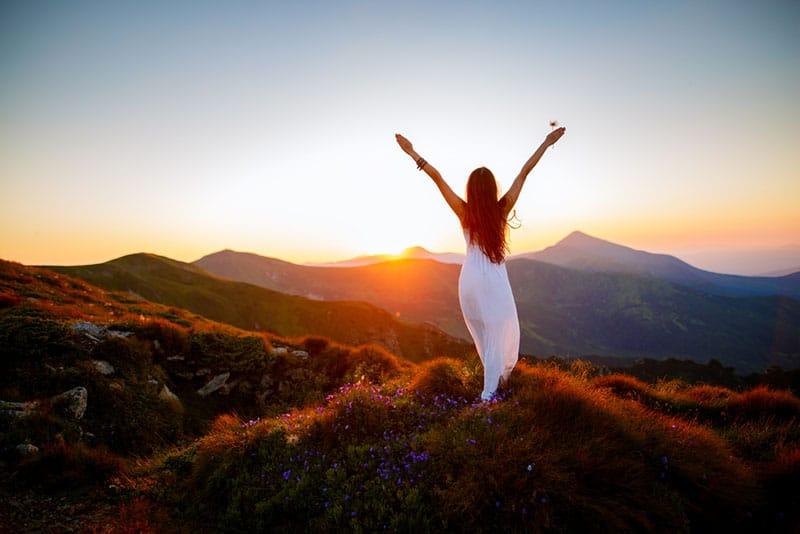 Frau im weißen Kleid, das auf dem Berg steht