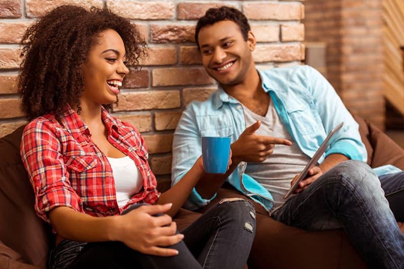 Afro-Frau, die mit ihrem Freund auf Tablette schaut
