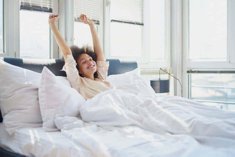 Afro-Frau, die sich morgens auf dem Bett ausdehnt