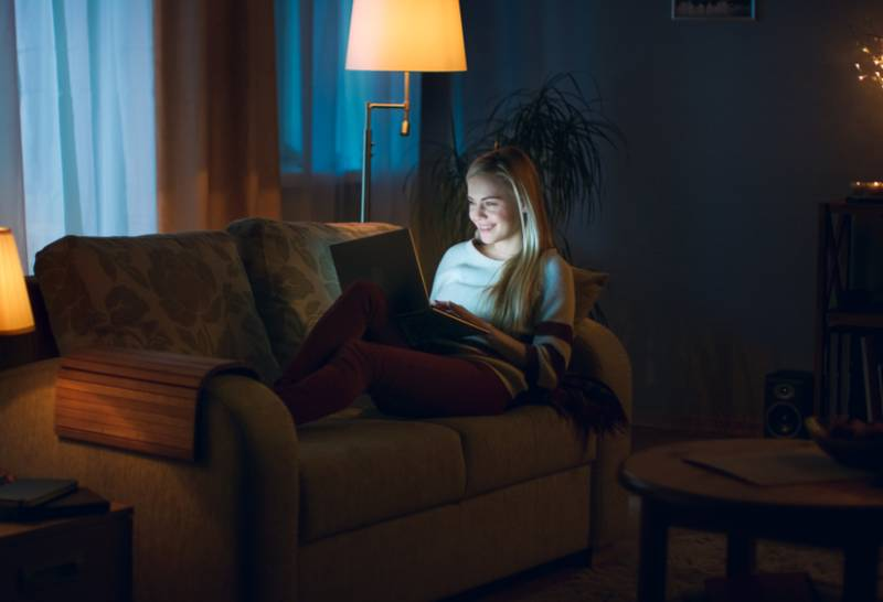 Am Abend liegt die schöne junge Frau mit einem Laptop auf der Couch