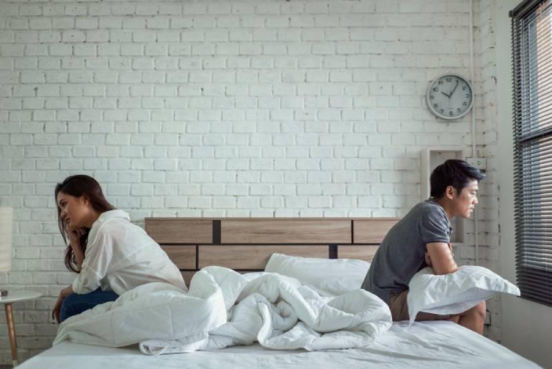 Asiatische Paare streiten sich im Bett, sie argumentieren, nicht miteinander zu reden