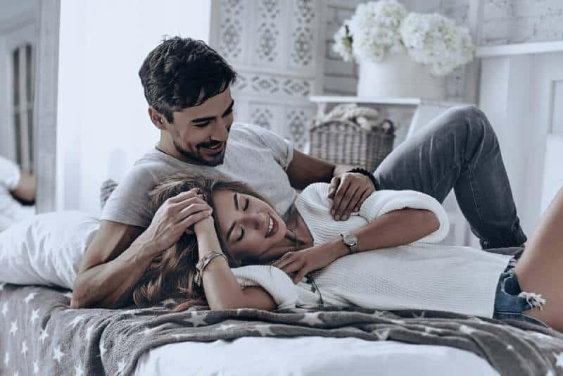 Attraktive junge Leute, die auf dem Bett liegen und lächeln, während sie Freizeit zu Hause verbringen