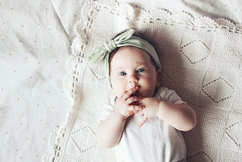 Baby, das Spitzenstirnband trägt