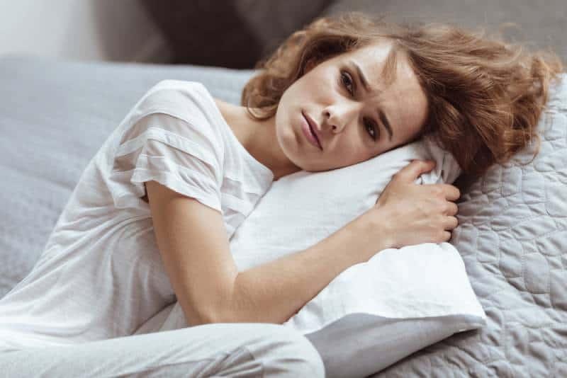 Besorgte reife Brünette, die auf einem Kissen liegt und an etwas Deprimierendes zu Hause denkt.