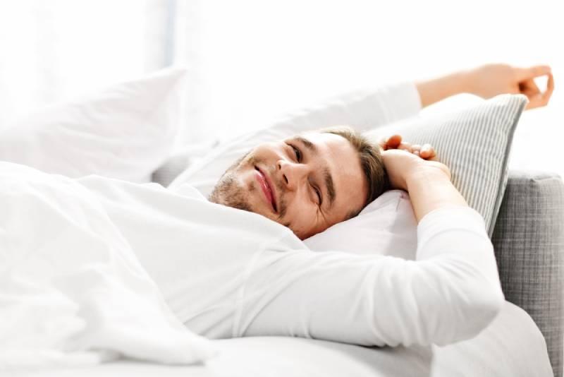 Bild zeigt jungen Mann, der sich im Bett ausdehnt