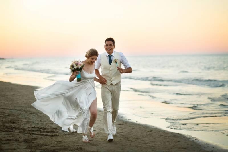 Bräutigam und Braut rennen gegen den Wind am Ufer entlang