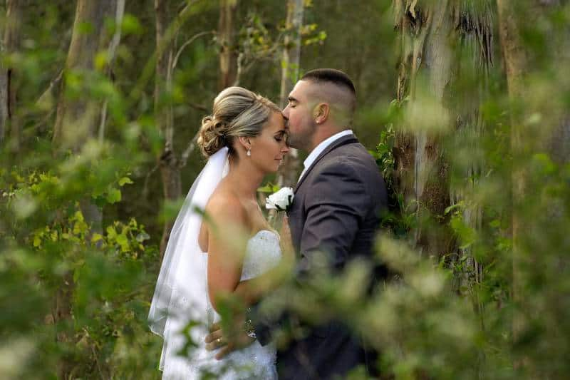 Bräutigam und Braut tagsüber küssen