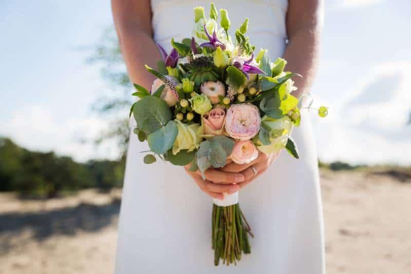 Braut hält ihren Hochzeitsstrauß mit bunten Blumen