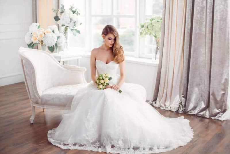 Braut im schönen Kleid sitzt auf Sofa drinnen im weißen Studio-Interieur wie zu Hause