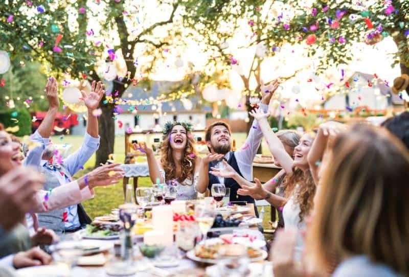 Braut und Bräutigam mit Gästen bei der Hochzeitsfeier draußen im Hinterhof.