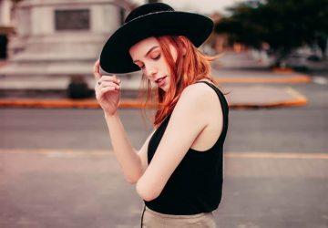 Auf der Straße steht eine Frau mit einem schwarzen Hut