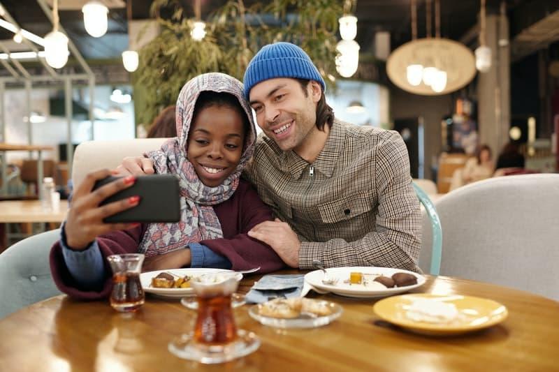 Das Paar macht Fotos beim Essen