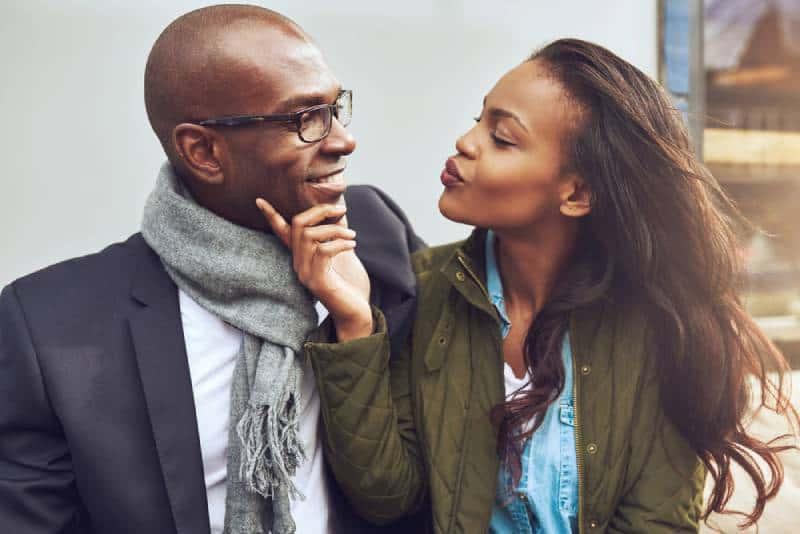 Das flirtende junge Mädchen berührt den Mann im Gesicht