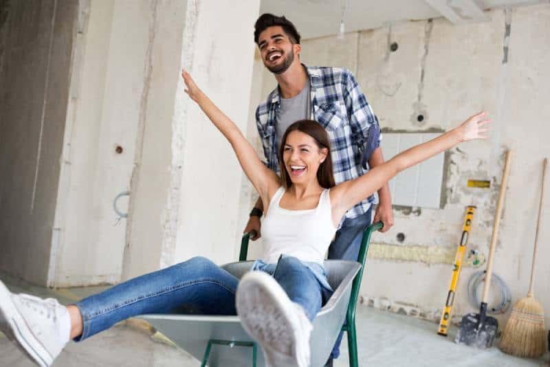 Das liebende Paar hat Spaß, während sie das Haus renovieren