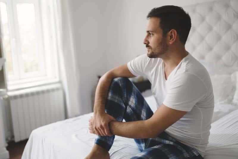 Der Mann sitzt auf dem Bett