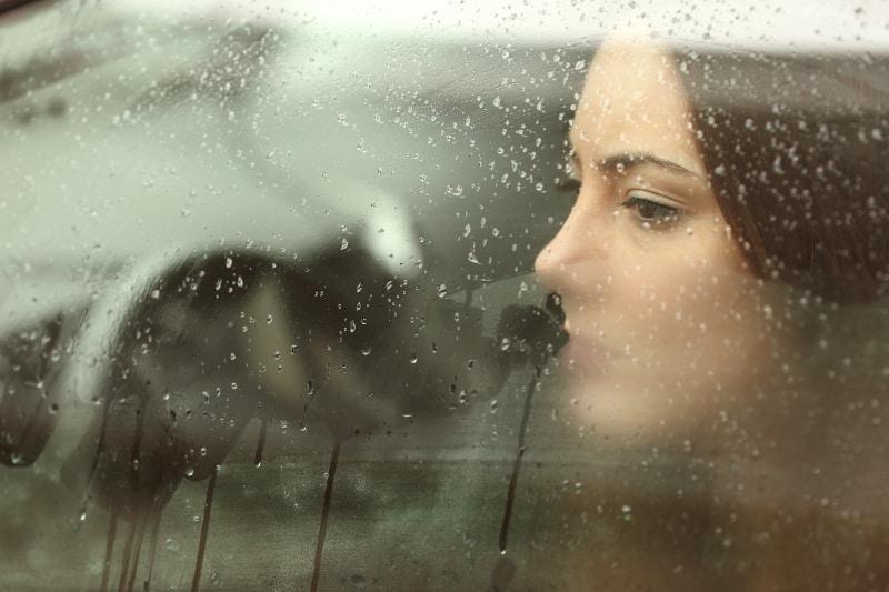 Die Frau schaut aus dem Fenster aus dem Auto