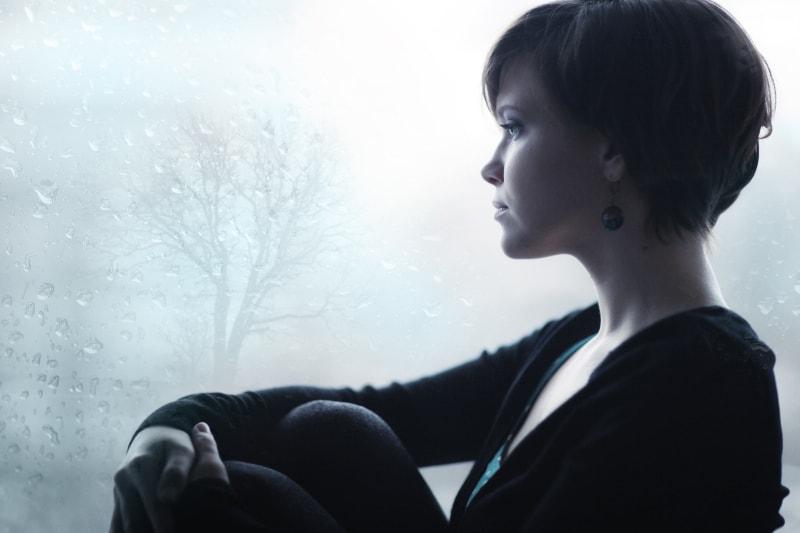 Die Frau schaut aus dem verschwommenen Fenster
