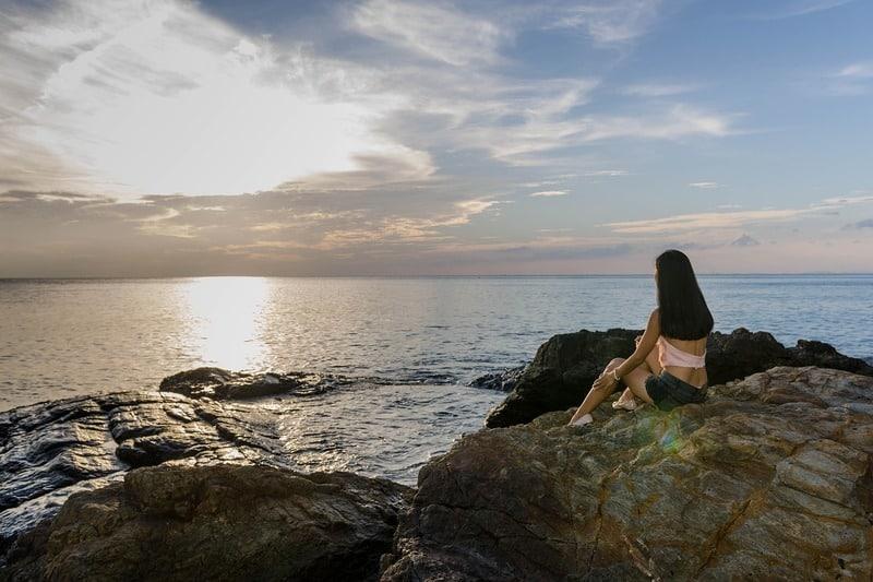 Die Frau sitzt am Meer